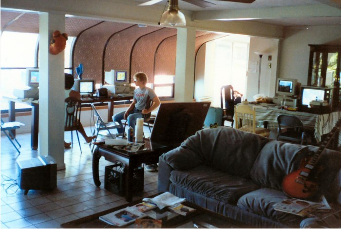 "A photo taken by Tom Hall in September 1990, at the lake house in Shreveport, LA, id Software's first office/bachelor pad. In the background, John Carmack (right) and John Romero work on the Super Mario Bros. 3 demo for Nintendo. Sitting in between their computers is an NES running Super Mario Bros. 3, which the ""two Johns"" played frequently to make sure they nailed the feel of the game. To the right, a desk holds Hall's equipment: a 386/33MHz PC running DOS, and an NES running Super Mario Bros. 3. To capture the exact look and feel of the NES classic, Hall paused the game and duplicated the artwork pixel by pixel. Photo credit: John Romero."
